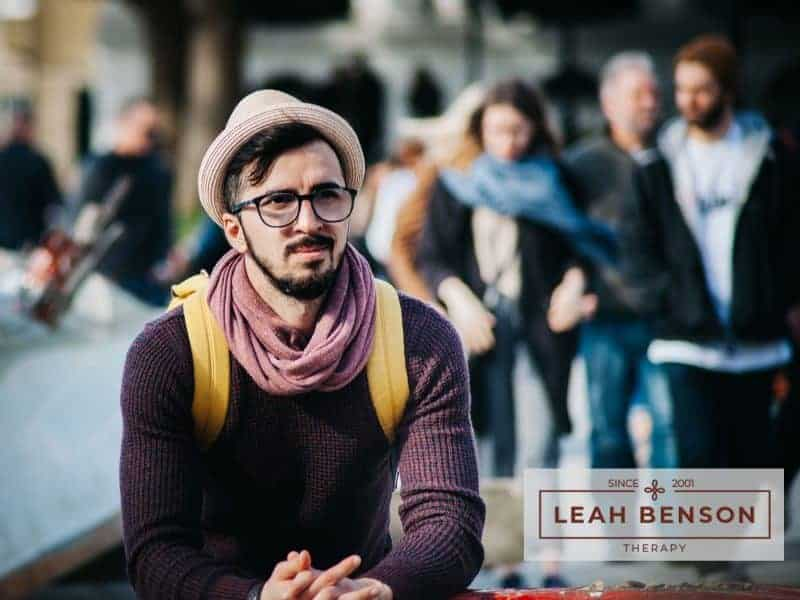Pensive man sitting alone and looking at a group of friends. Text says LEAH BENSON THERAPY