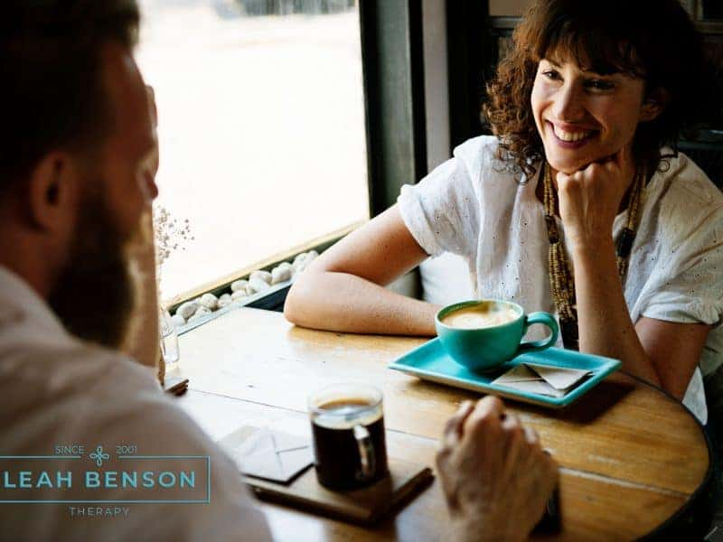 Friendly couple enjoying each others' company. Leah Benson Therapy logo on photo