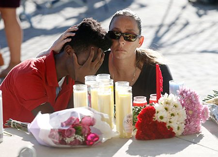 Photo of mourning children with flowers and candles