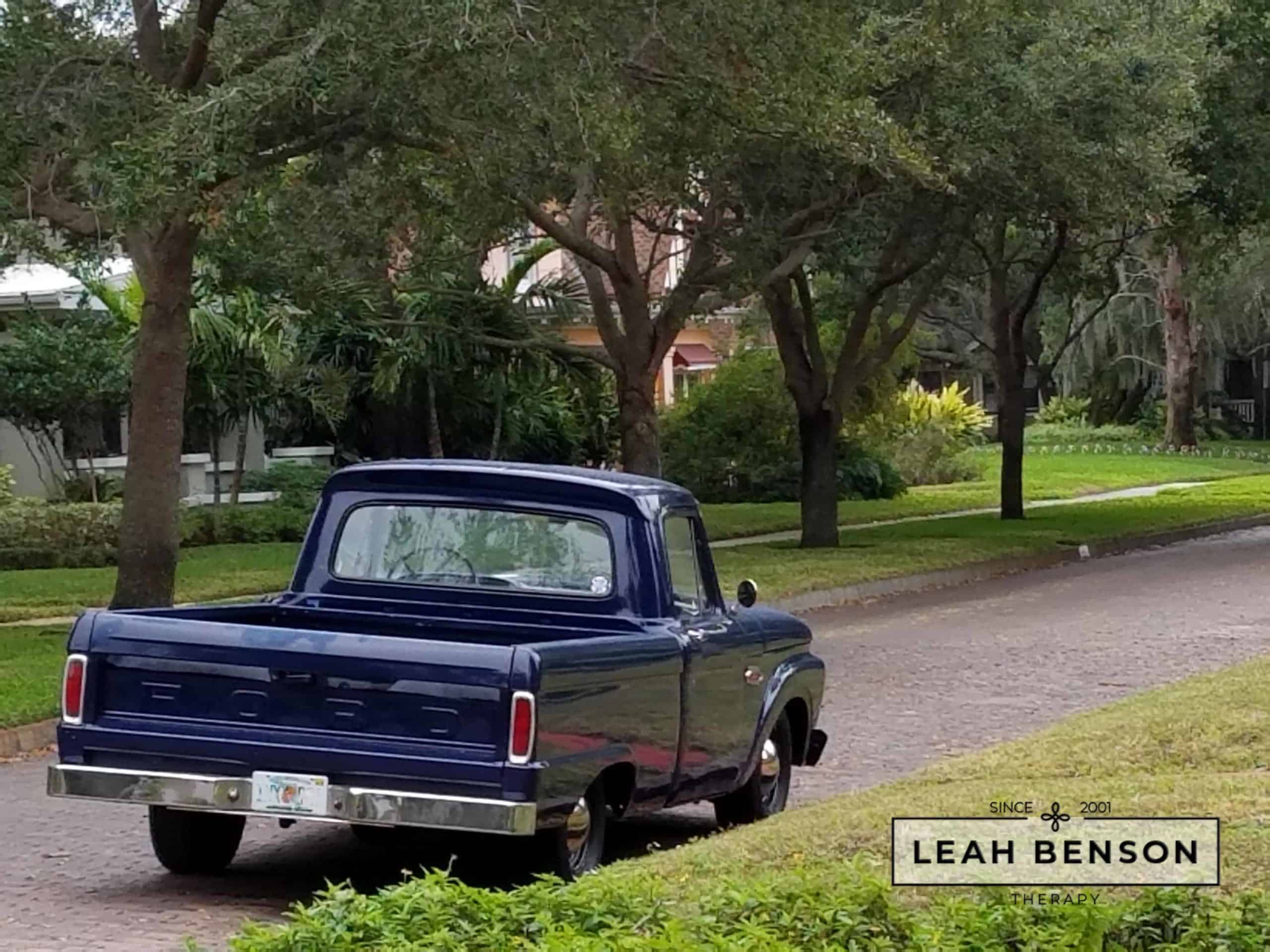 1960's blue Ford pickup truck parked in the Old Northeast of St Petersburg with the logo of Leah Benson Therapy
