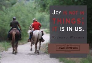 "Photo of 2 horsemen on a trail with text, ""Joy isn't in Things, It's In Us"""