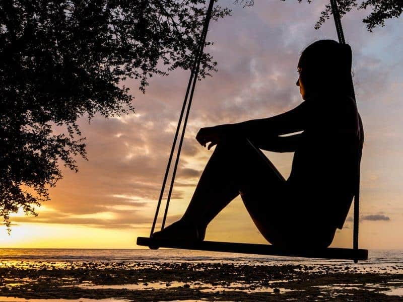 Woman on a swing looking at sunset