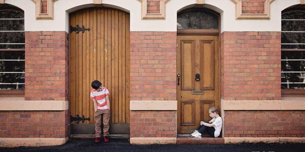 Photo by Kat Jayne of two boys, one in each doorway. Logo of Leah Benson Therapy