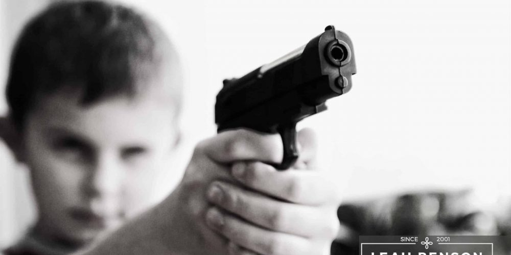 Young boy pointing a toy pistol near the camera. Text says LEAH BENSON THERAPY