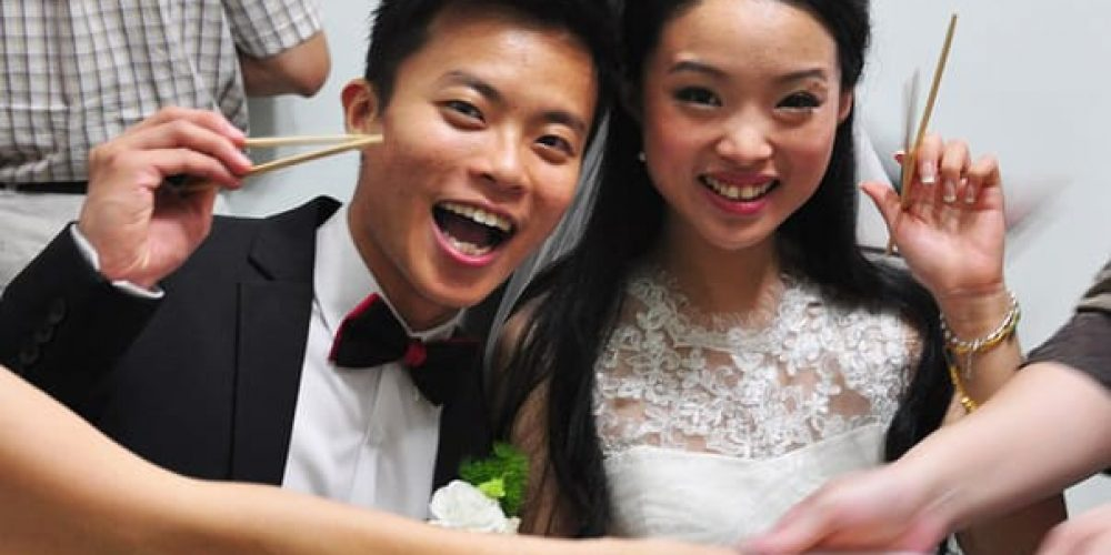cute asian couple at their wedding holding chopsticks